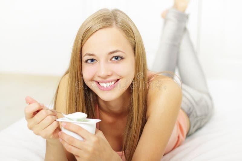 Muchacha atractiva que come el yogur foto de archivo