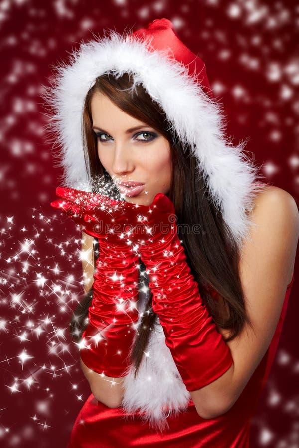 Muchacha atractiva que desgasta la ropa de Papá Noel en r fotografía de archivo libre de regalías