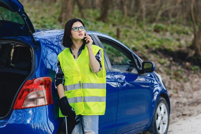muchacha atractiva que habla por el teléfono cerca del coche en el camino en enchufe de la seguridad foto de archivo libre de regalías