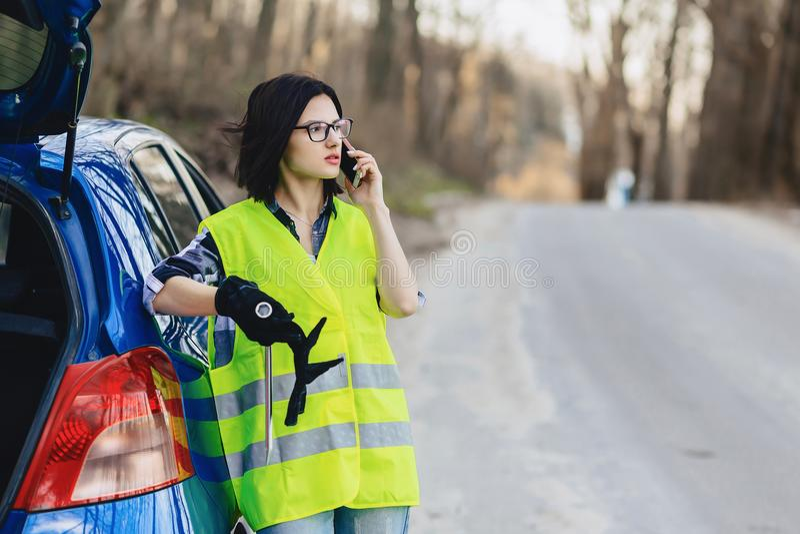 muchacha atractiva que habla por el teléfono cerca del coche en el camino en enchufe de la seguridad fotografía de archivo libre de regalías