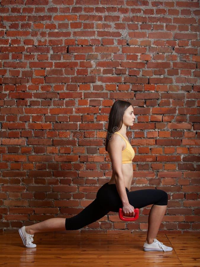 Muchacha atractiva que hace estocadas con pesas de gimnasia foto de archivo