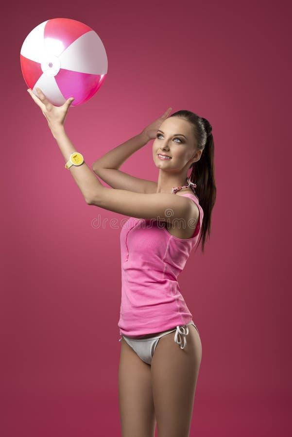 Muchacha atractiva que juega con la pelota de playa fotos de archivo
