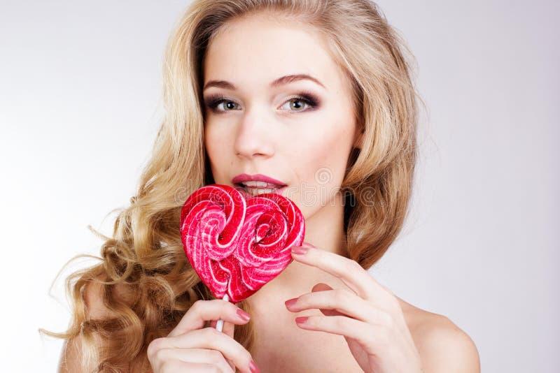 Muchacha atractiva que lleva el vestido rosado con el caramelo. foto de archivo libre de regalías