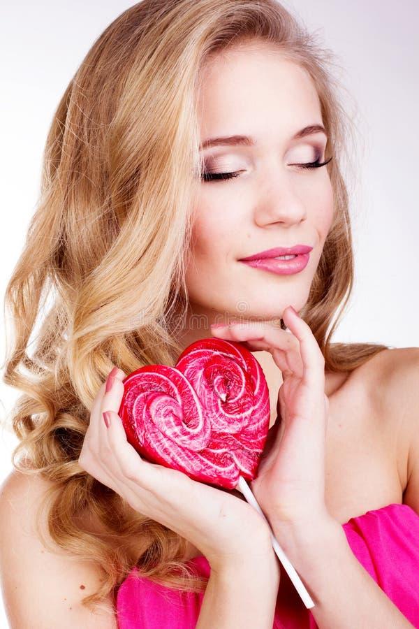Muchacha atractiva que lleva el vestido rosado con el caramelo. fotografía de archivo