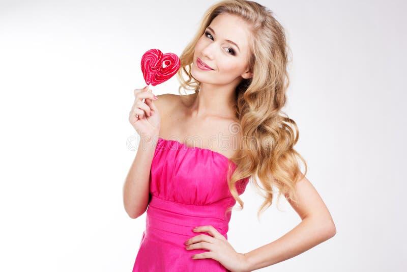 Muchacha atractiva que lleva el vestido rosado con el caramelo imagen de archivo libre de regalías