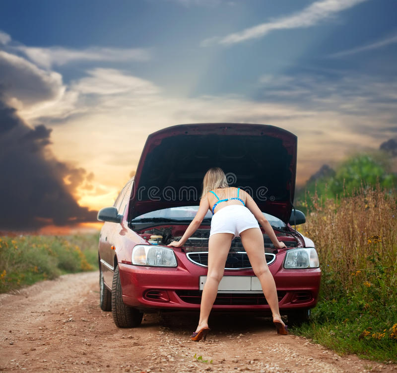 Muchacha atractiva que mira bajo el capo motor del coche foto de archivo