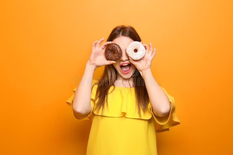 Muchacha atractiva que presenta con los buñuelos en fondo del color fotos de archivo libres de regalías