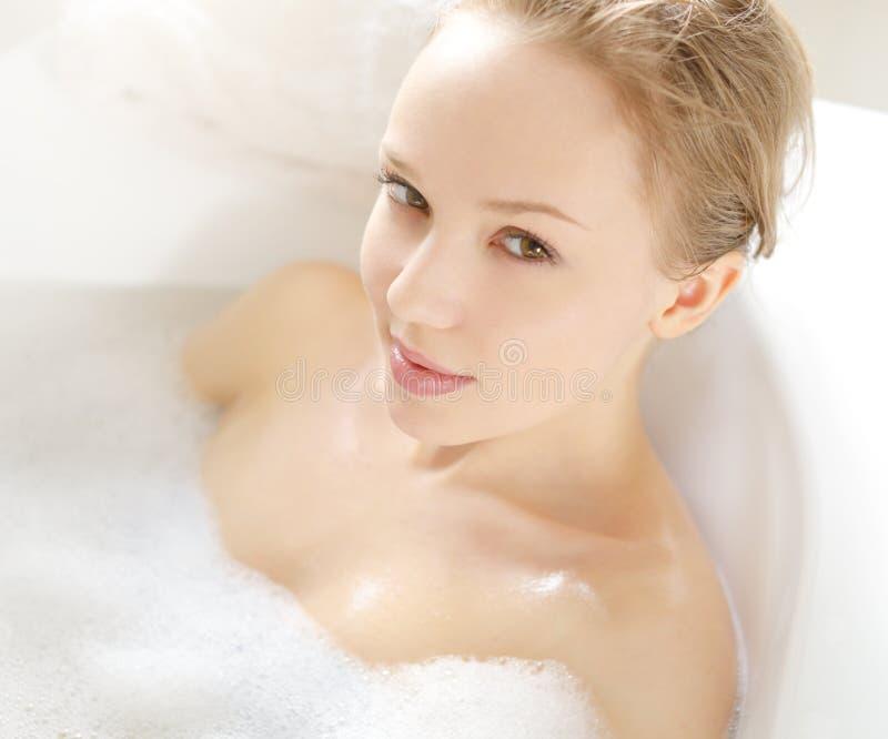 Muchacha atractiva que se relaja en baño foto de archivo