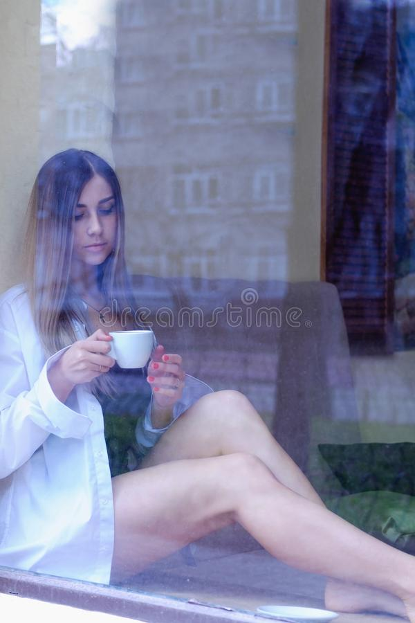 Muchacha atractiva que se sienta cerca de la ventana y del café de consumición escoja a la mujer en la camisa de los hombres blan imagen de archivo libre de regalías
