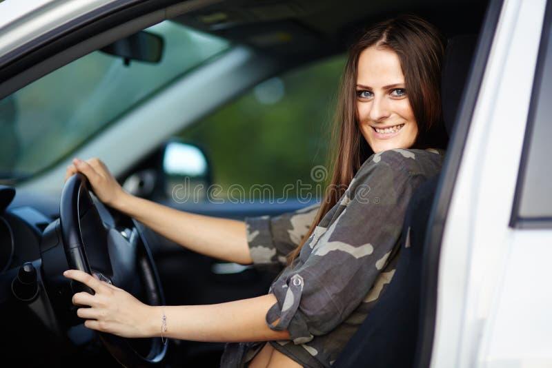 Muchacha atractiva que se sienta en el coche foto de archivo libre de regalías