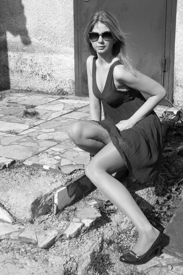 Muchacha atractiva que se sienta en las escaleras fotos de archivo