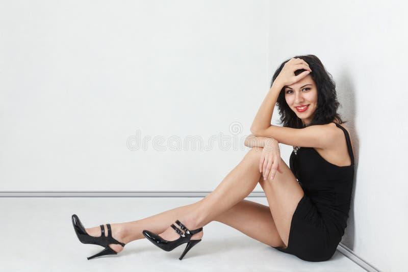 Muchacha atractiva que se sienta en suelo foto de archivo