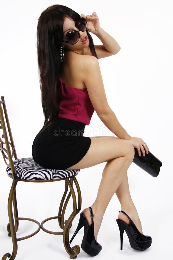 Muchacha atractiva que se sienta en una silla foto de archivo