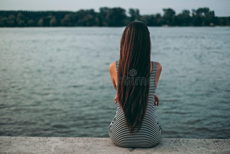 Muchacha atractiva que se sienta solamente por el agua imagen de archivo