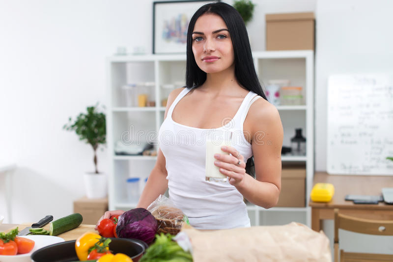 Muchacha atractiva que sostiene el vidrio de leche, comiendo el bocado sano mientras que prepara el plato vegetal El cocinar feme fotos de archivo