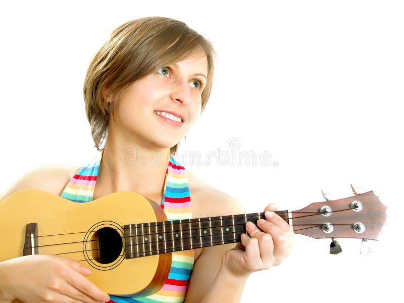 Muchacha atractiva que toca una guitarra hawaiana fotografía de archivo