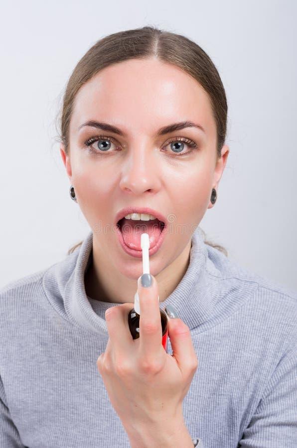 Muchacha atractiva que toma una medicina con el espray dentro de la garganta en fondo ligero imagen de archivo libre de regalías