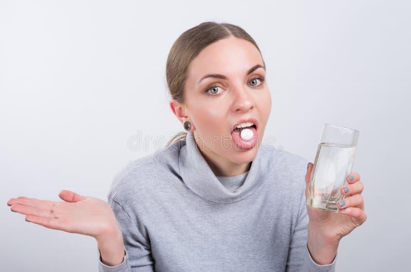 Muchacha atractiva que toma una píldora con agua en fondo ligero fotografía de archivo