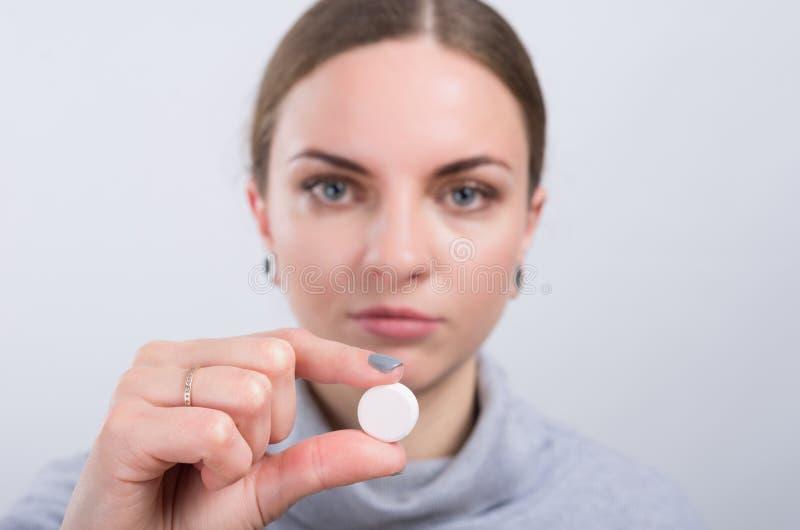 Muchacha atractiva que toma una píldora en fondo ligero imagenes de archivo