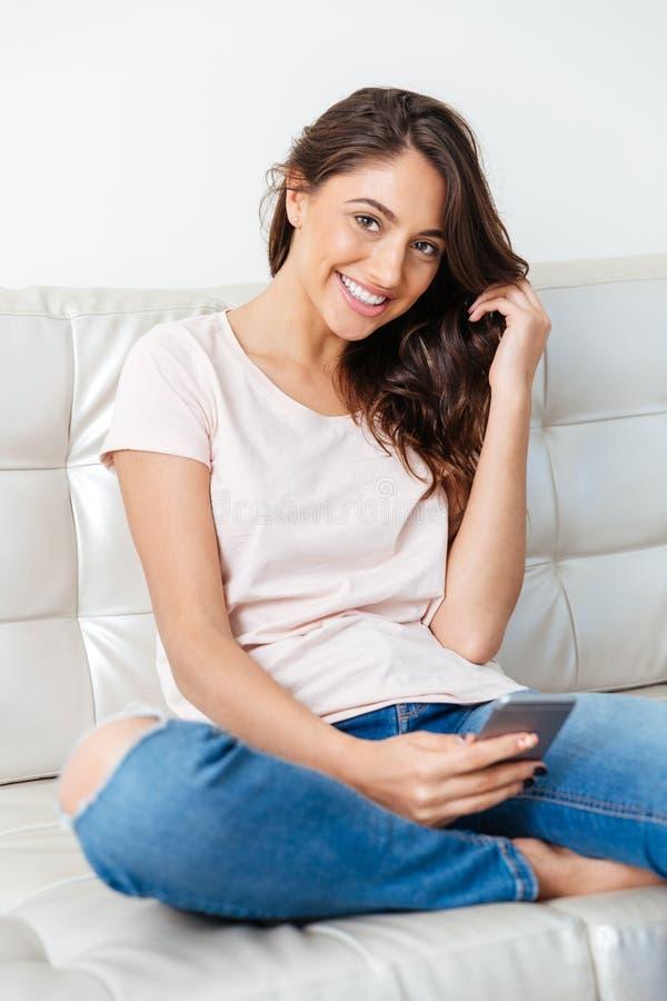 Muchacha atractiva que usa el teléfono elegante sobre el fondo blanco fotos de archivo libres de regalías