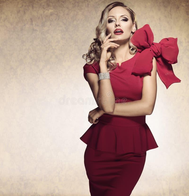 Muchacha atractiva rubia arrogante. vestido rojo imagenes de archivo