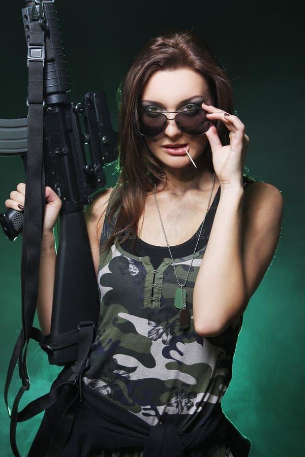 Muchacha atractiva y atractiva del ejército con el rifle de asalto fotografía de archivo