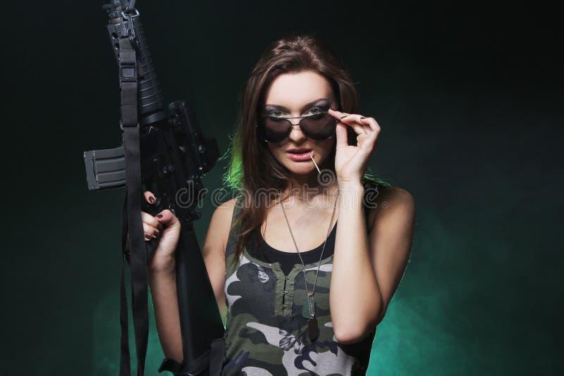 Muchacha atractiva y atractiva del ejército con el rifle de asalto foto de archivo libre de regalías