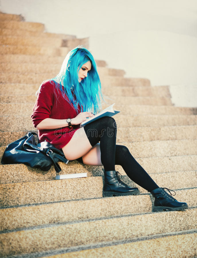 Muchacha azul-cabelluda bastante joven del grunge que se sienta en las escaleras y que lee un libro fotos de archivo libres de regalías