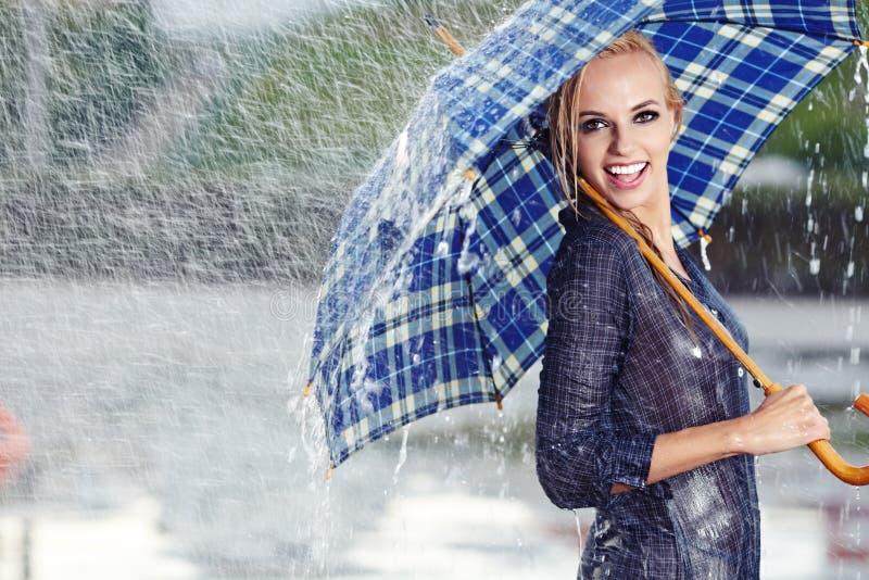 Muchacha bajo el paraguas que mira la lluvia imagen de archivo libre de regalías