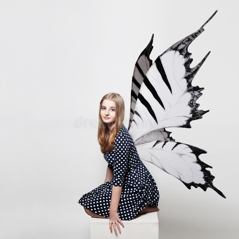 Muchacha bastante adolescente con las alas de la mariposa imagen de archivo