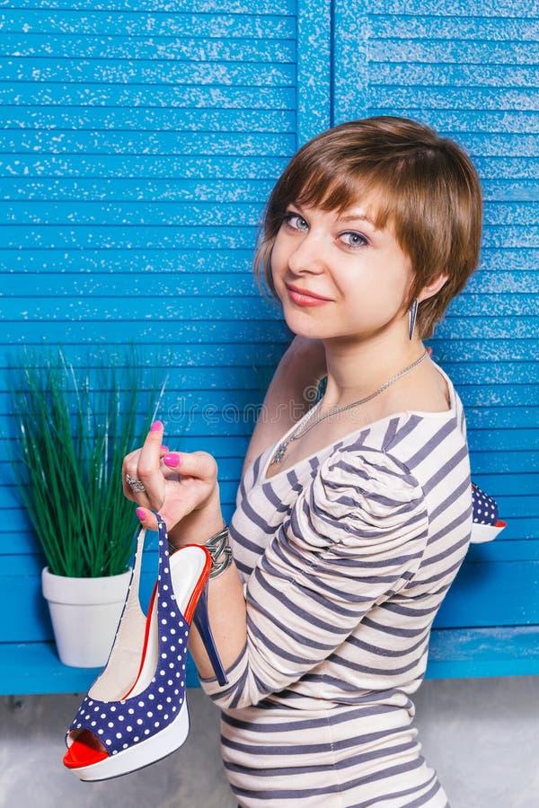 Muchacha bastante adolescente que sostiene los nuevos zapatos punteados de tacón alto en su finger Ventana azul de la persiana co imagenes de archivo