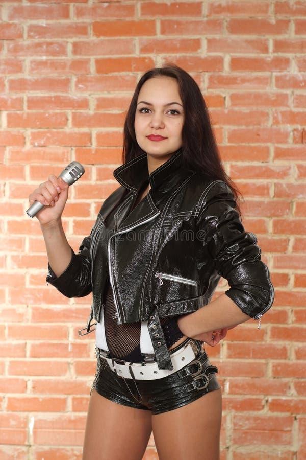 Muchacha bastante agradable con un micrófono fotos de archivo