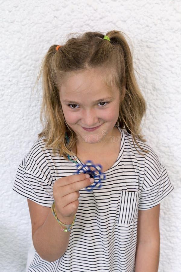 Muchacha bastante de siete años que juega con el hilandero de la mano del juguete fotos de archivo