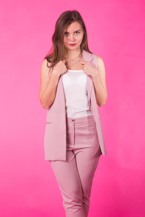 Muchacha bastante elegante con el pelo largo que presenta contra fondo rosado Retrato de la moda de la mujer sonriente feliz jove fotografía de archivo