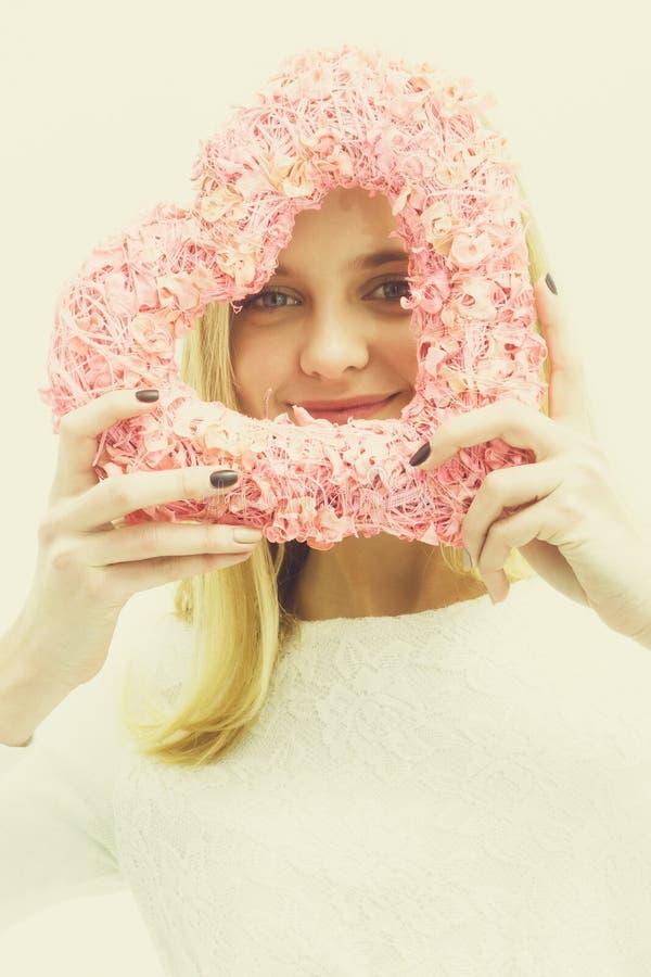 Muchacha bastante feliz con el corazón de mimbre rosado para el día de tarjetas del día de San Valentín imagenes de archivo