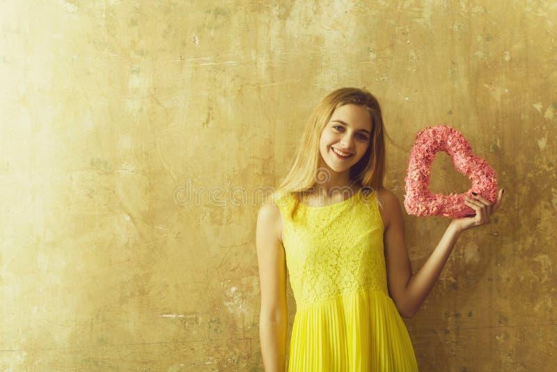 Muchacha bastante feliz con el coraz?n de mimbre rosado para el d?a de tarjetas del d?a de San Valent?n foto de archivo libre de regalías