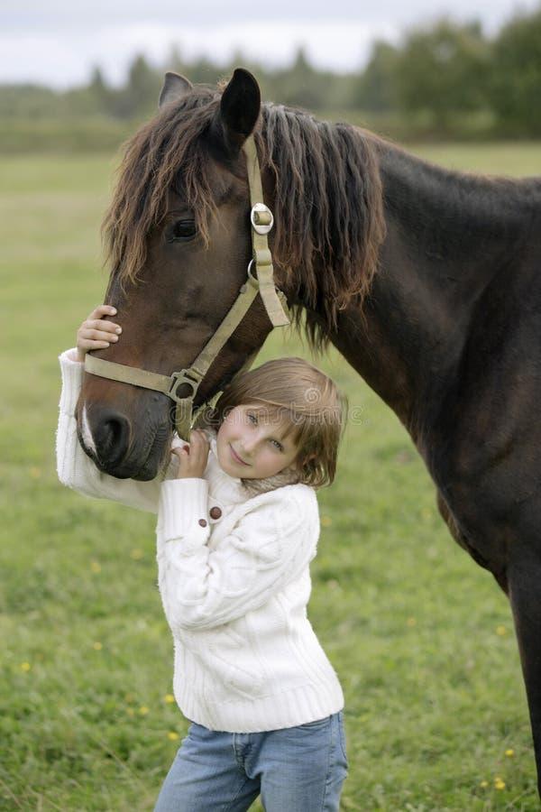 Muchacha bastante feliz en un suéter blanco y los vaqueros que sostienen el caballo por la sonrisa con tirante y espalda descubie imagenes de archivo