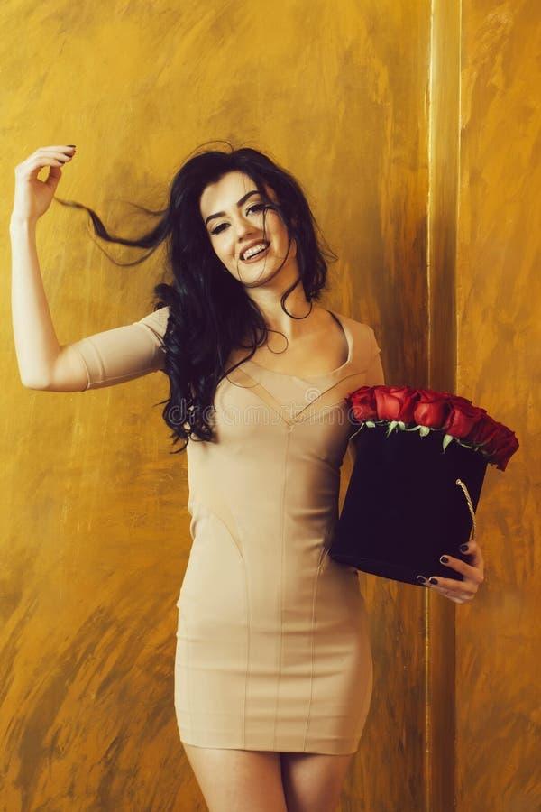 Muchacha bastante feliz que sonríe con las rosas rojas en caja fotografía de archivo libre de regalías
