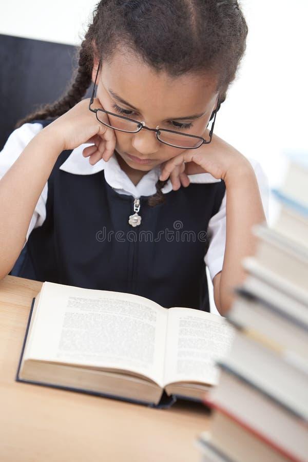 Muchacha bastante joven de la escuela que lee un libro imagen de archivo