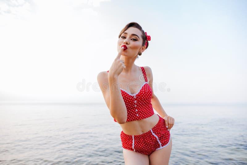Muchacha bastante modela feliz en el traje de baño rojo que envía un beso imagen de archivo libre de regalías