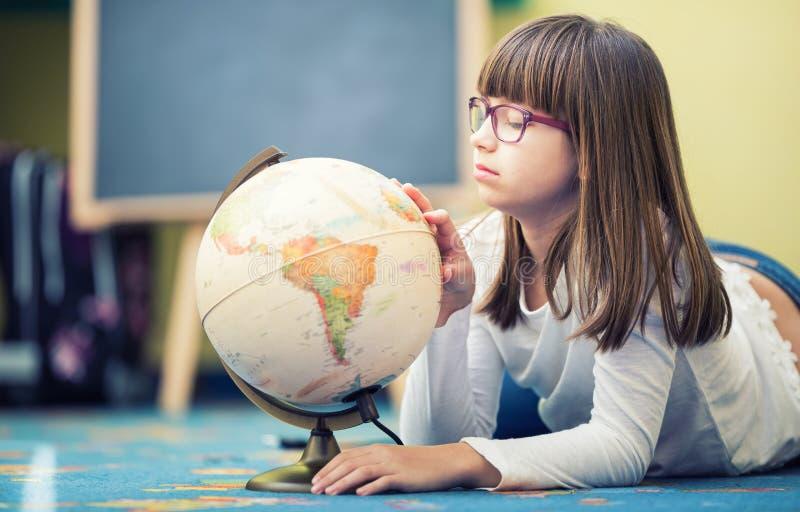 Muchacha bastante pequeña del estudiante que estudia la geografía con el globo en un cuarto de niño foto de archivo libre de regalías