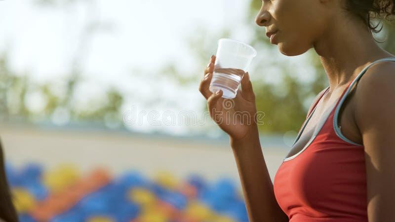 Muchacha Biracial que bebe después del entrenamiento, restableciendo el equilibrio de agua, hidración imagen de archivo