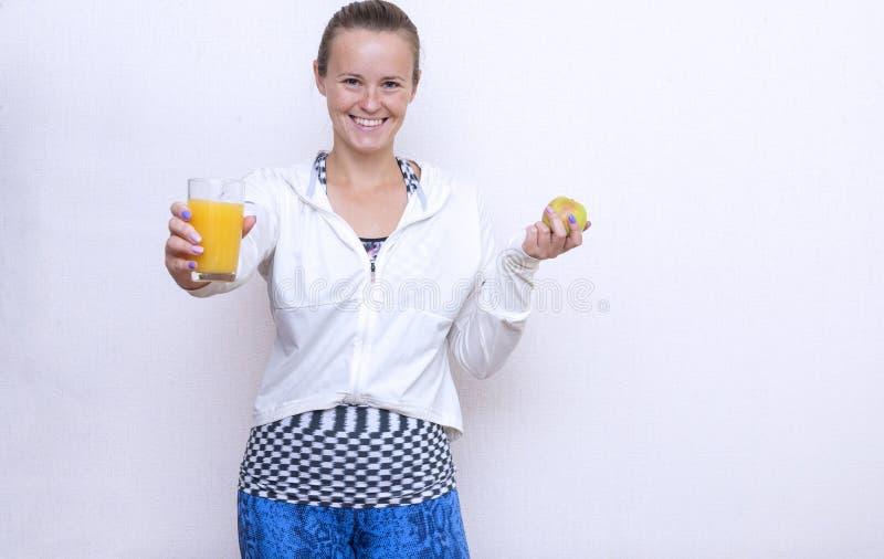 1 muchacha blanca en los deportes blancos remata sostener Apple y un vidrio de zumo de naranja, sonrisa de la mujer joven fotos de archivo libres de regalías