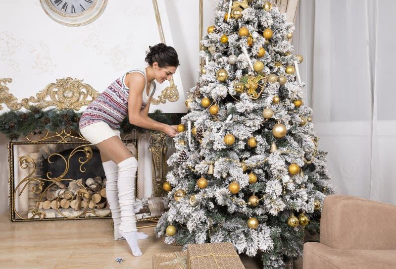 1 muchacha blanca en un vestido hecho punto adorna un árbol de navidad en ho fotografía de archivo