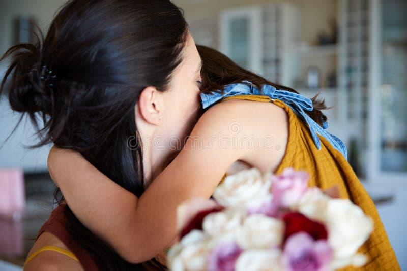 Muchacha blanca joven que abraza a su madre después de dar sus flores como regalo en su cumpleaños, cierre para arriba fotografía de archivo
