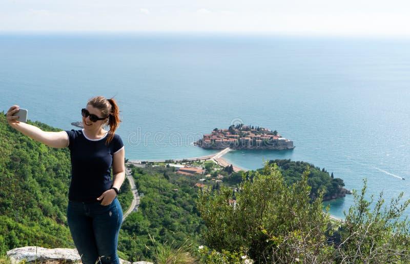 Muchacha blanca joven que hace un selfie en la montaña y el mar adriático en el fondo y Sveti Stefan Mujer con el teléfono elegan foto de archivo libre de regalías