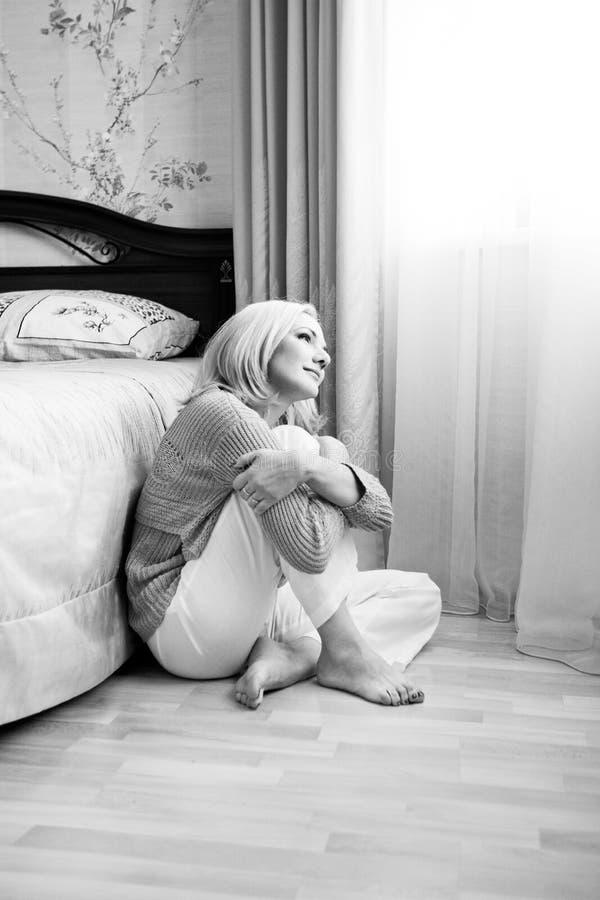 Muchacha blanco y negro que se sienta en el piso a piernas cruzadas en interior foto de archivo libre de regalías