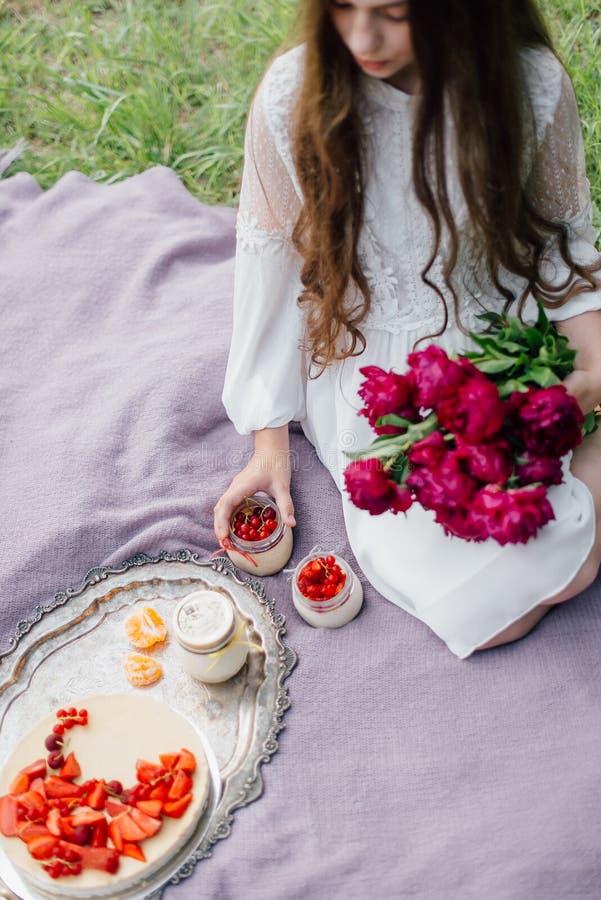 Muchacha blanda con encendido una comida campestre con los pasteles de queso y las peonías fotos de archivo libres de regalías