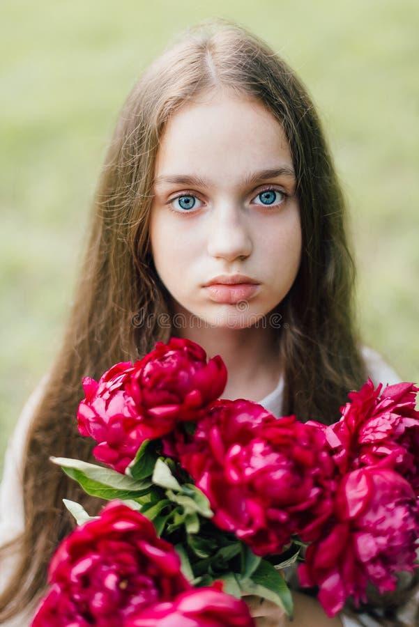 Muchacha blanda con los ojos azules que sostienen la peonía púrpura suave foto de archivo