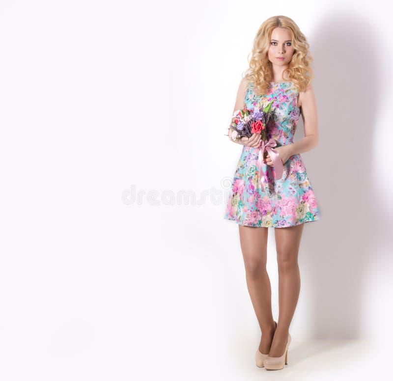 Muchacha blanda dulce modesta atractiva hermosa con el pelo rubio rizado que se coloca en el fondo blanco con un ramo de flores d imágenes de archivo libres de regalías